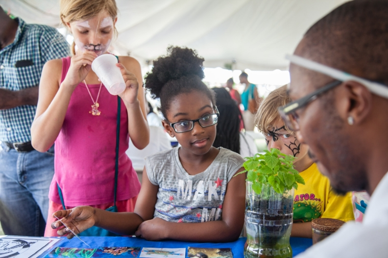 Afternoon on the Green 2016 photo: young girl intrigued at UVI booth