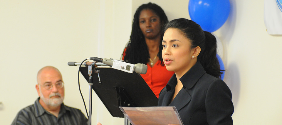 UVI graduate April Fale-Knight announces the launch of WUVI , while UVI communications Professor Dr. Alexander Randall (left) and UVI communications graduate Leslyn Tonge stand in the background.