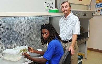 University of the Virgin Islands Assistant Director of Agricultural Experiment Station Thomas Zimmerman assists student.