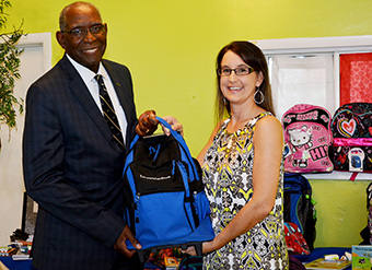 UVI President David Hall presents a backpack to Dana Holtz, Queen Louise Home for Children director.