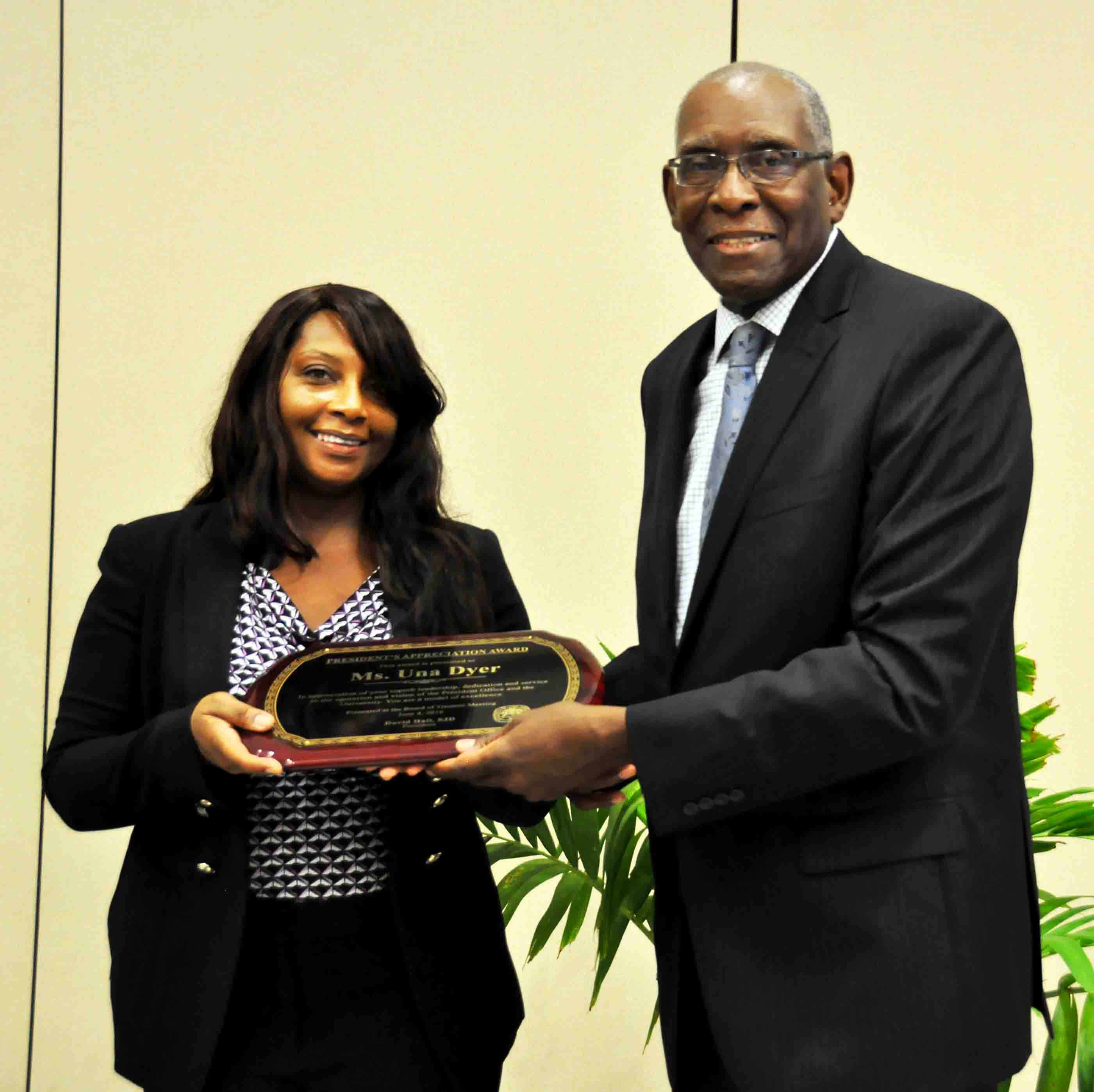 Una Dyer accepts award from UVI President David Hall