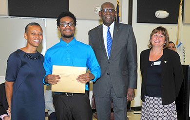 A student Receives his Award from President David Hall and Provost Camille Mc Kayle